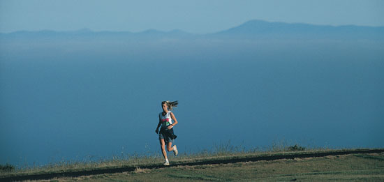 Student running on track overlooking ocean and mountains
